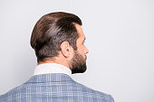 Half-face back side view close up portrait of stunning man with modern haircut and bristle isolated on gray background