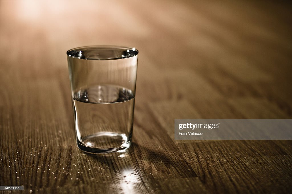 Half-filled glass of water on table : Stock Photo