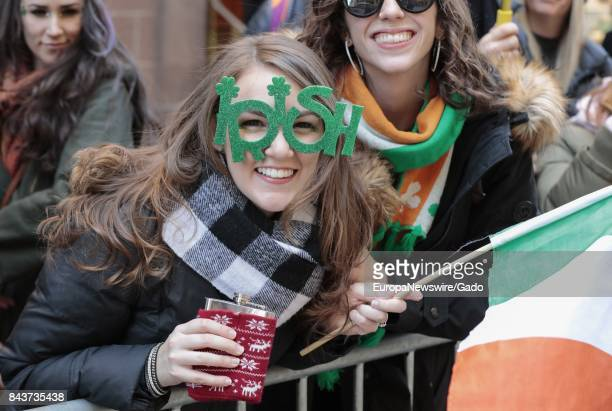Halflength portrait of a millennial generation woman holding a flask and Irish flag with novelty glasses that read 'Irish' leaning over a fence and...
