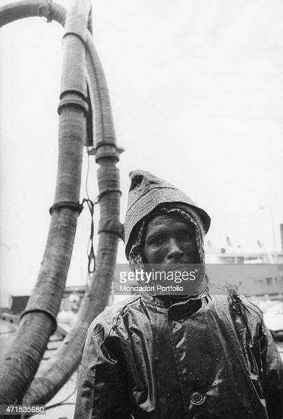'Halflength portrait of a worker wearing a mac with hood behind him can be seen big ropes of pumps for fuel extraction Kuwait City December 1956 '
