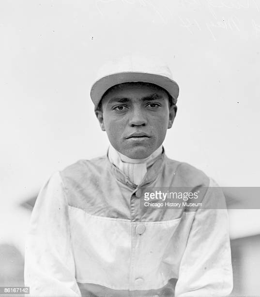Halflength portrait of jockey Knight an African American man wearing racing silks and cap standing outdoors on the roof of the paddock stable at...
