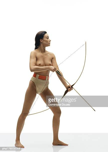 Half-nude woman holding bow and arrow, side view