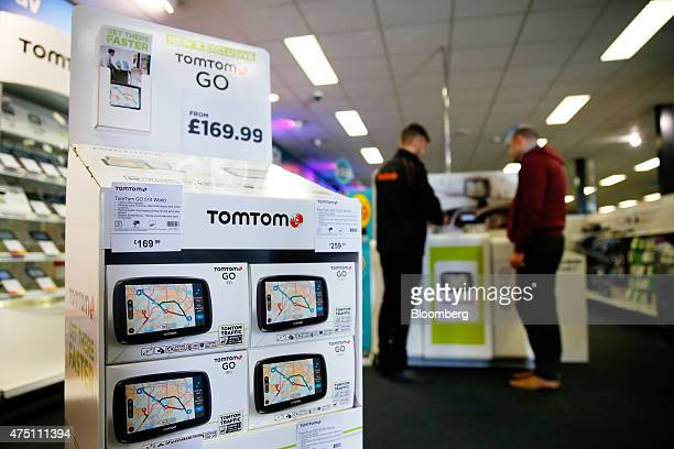 A Halfords employee demonstrates navigation systems manufactured by TomTom NV to a customer at a Halfords Group Plc store in Manchester UK on Friday...