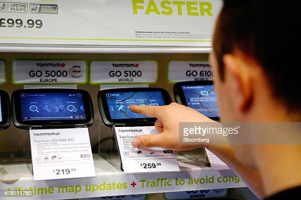 A Halfords employee uses the touchscreen on a TomTom Go 5100 navigation system manufactured by TomTom NV inside the Halfords Group Plc store in...