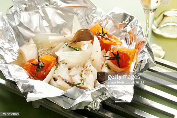 Halibut in aluminium foil with tomatoes and mushrooms