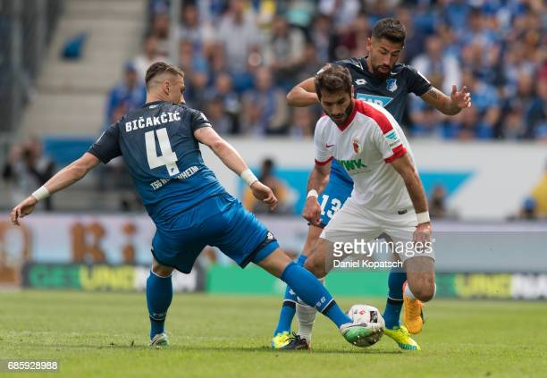 Halil Altintop of Augsburg is challenged by Ermin Bicakcic of Hoffenheim and Kerem Damirbay of Hoffenheim during the Bundesliga match between TSG...
