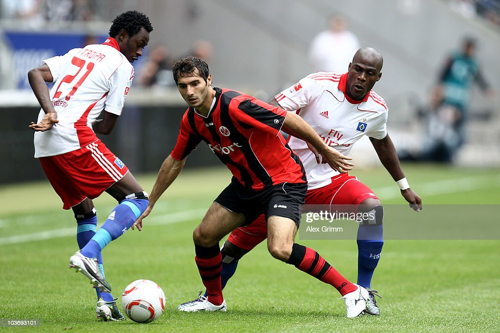 Halil Altintop (C) of Frankfurt is challenged by Jonathan Pitroipa (L) and Guy Demel of Hamburg during the Bundesliga match between Eintracht Frankfurt and Hamburger SV at the Commerzbank Arena on August 28, 2010 in Frankfurt am Main, Germany.