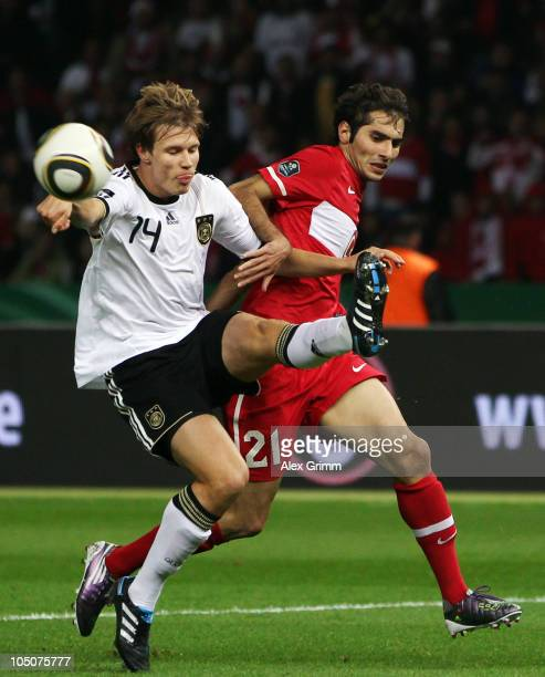 Halil Altintop of Turkey is challenged by Holger Badstuber of Germany during the EURO 2012 group A qualifier match between Germany and Turkey at the...