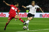 Halil Altintop of Turkey is challenged by Per Mertesacker of Germany during the EURO 2012 group A qualifier match between Germany and Turkey at the...