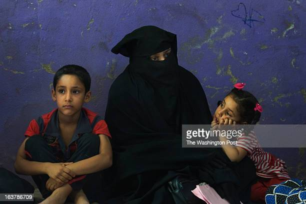 Halima Daham who is still officially mourning the recent death of her husband sits with two of her six children Ali Khamas L and Fatima Khamas 5 at...