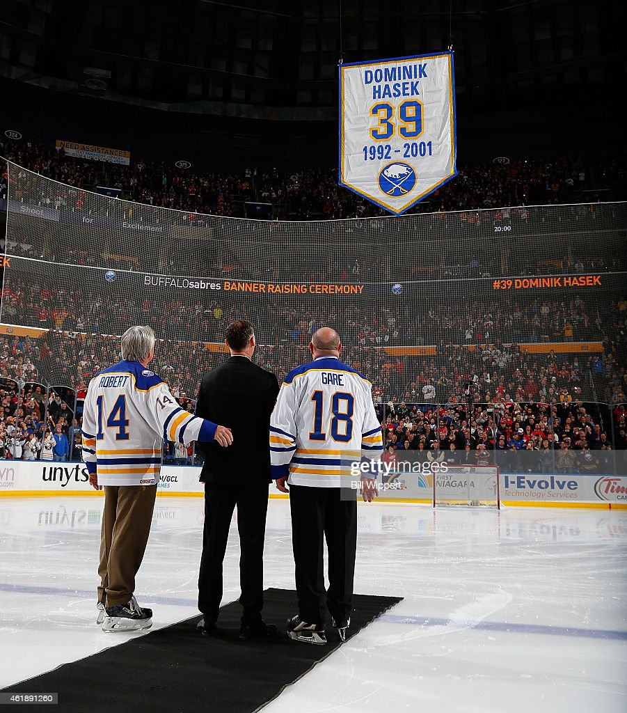 Hall of Fame goaltender Dominik Hasek of the Buffalo Sabres stands between former Sabres Rene Robert and Danny Gare during ceremonies to retire his...