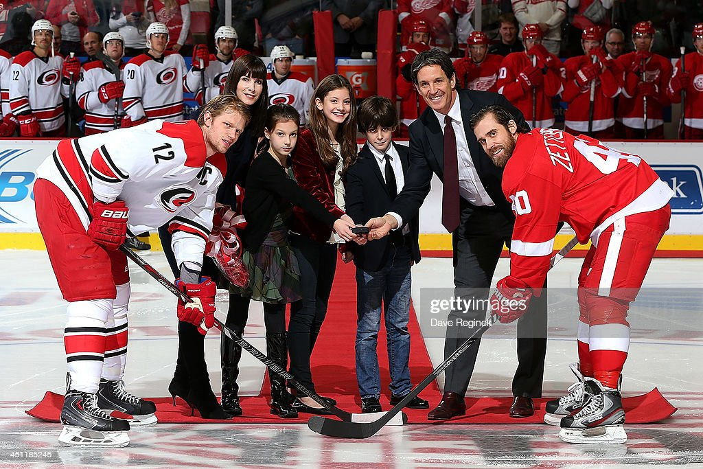 Hall of fame inductee and former Red Wing Brendan Shanahan accompanied by his wife Catherine, son Jake and daughters Maggie and Catherine drops the ceremonial puck for captains Eric Staal #12 of the Carolina Hurricanes and Henrik Zetterberg #40 of the Detroit Red Wings as he is honored before an NHL game at Joe Louis Arena on November 21, 2013 in Detroit, Michigan.