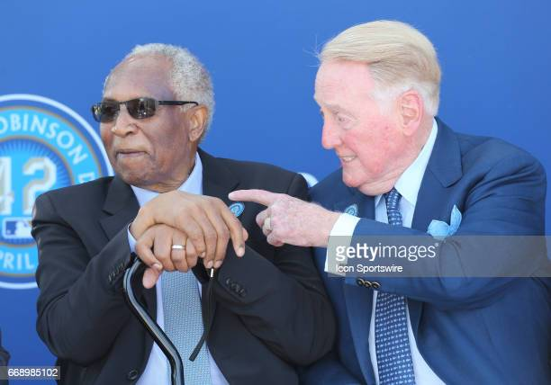 Hall of Fame manager Frank Robinson talks with announcer Vin Scully during the Jackie Robinson statue unveiling before the game against the Arizona...