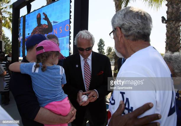 Hall of Fame pitcher Sandy Koufax and former catcher Steve Yaeger sign an autograph for a fan during the Jackie Robinson statue unveiling before the...