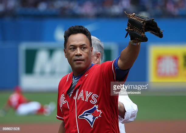 Hall of Fame player Roberto Alomar of the Toronto Blue Jays acknowledges fans after catching a ceremonial first pitch from former general manager and...