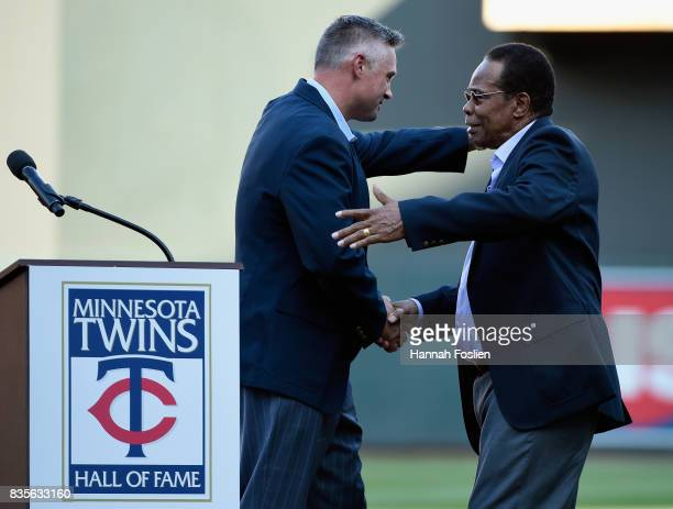 Hall of fame player Rod Carew hugs Micheal Cuddyer as he is inducted into the Minnesota Twins Hall of Fame in a ceremony before the game between the...