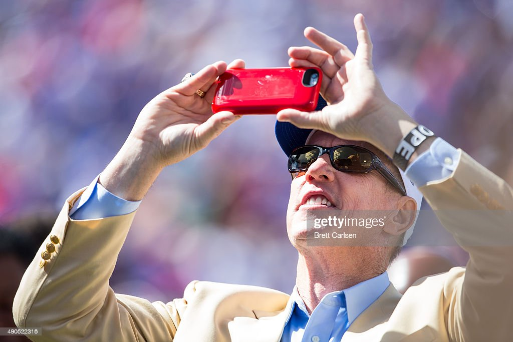 Hall of Fame quarterback <a gi-track='captionPersonalityLinkClicked' href=/galleries/search?phrase=Jim+Kelly+-+American+Football+Player&family=editorial&specificpeople=216547 ng-click='$event.stopPropagation()'>Jim Kelly</a> takes photographs with his smartphone before the game between the Buffalo Bills and the New England Patriots on September 20, 2015 at Ralph Wilson Stadium in Orchard Park, New York. New England defeats Buffalo 40-32.