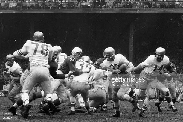 Hall of Fame quarterback YA Tittle of the San Francisco 49ers completes a handoff to fullback Gene Babb during the 49ers 3110 loss to the Detroit...