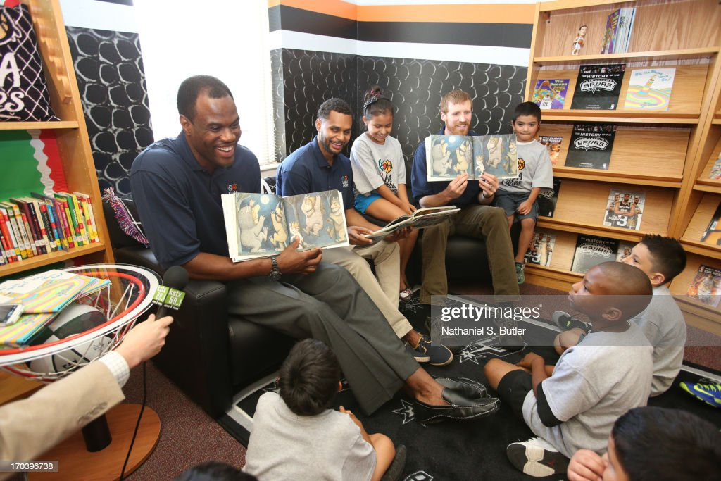 Hall of Famer David Robinson, Patty Mills and Matt Bonner of the San Antonio Spurs reads to the kids at the 2013 NBA Cares Legacy Project as part of the 2013 NBA Finals on June 7, 2013 at the Wheatley Middle School in San Antonio, Texas.