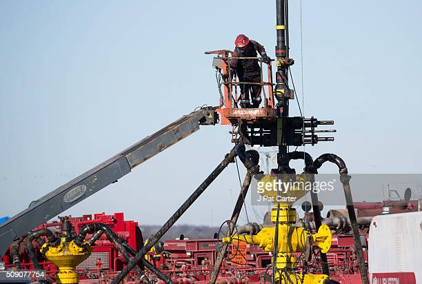Halliburton oil well fielder works on a well head at a fracking rig site January 27 2016 near Stillwater Oklahoma
