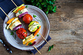 Halloumi cheese and vegetables grilled skewers on plate with spices and herbs close up - healthy vegetarian vegan diet barbecue grilled vegetable homemade meal
