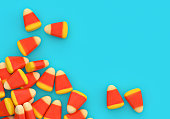 Halloween candy corn corner border over blue background with copy space