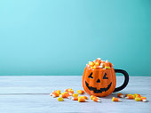 Halloween celebration concept with candy corn and jack o lantern cup on wooden table.