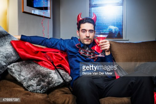 Halloween devil relaxing on sofa with cocktail.