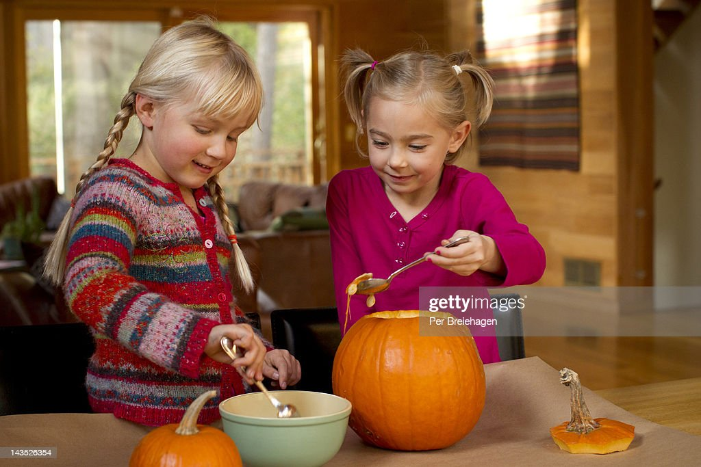 Halloween girls carving pumpkin : Stock Photo