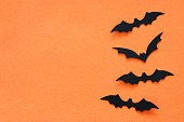 Halloween holiday concept. Black bats over orange background. Top view, flat lay