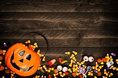 Halloween Jack o Lantern pail with bottom border of spilling candy. Above view on a rustic wood background with copy space.