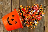 Halloween Jack o Lantern pail with spilling candy, above view on a rustic wood background
