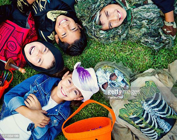halloween kids laying on grass