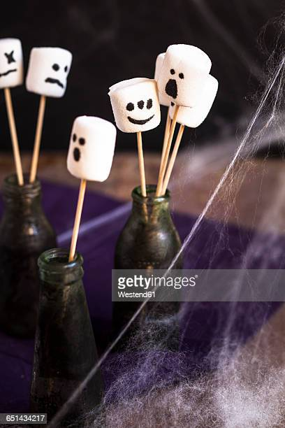 Halloween marshmallows with ghost faces on skewers