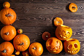 Halloween pumpkins over wooden background, top view, flat lay with copy space for text