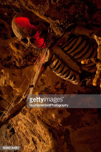 Halloween Skeleton hung on cave wall of ghost walk : Stock Photo