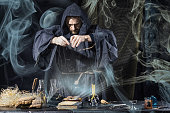 Halloween. The medieval alchemist holds magic ritual at the table in his laboratory smoke in the background