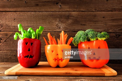 Halloween vegetables and dip in Jack o Lantern peppers on a wood background : Stock Photo