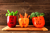 Healthy Halloween food. Vegetables for dipping in Jack o Lantern bell peppers. Side view against rustic wood.