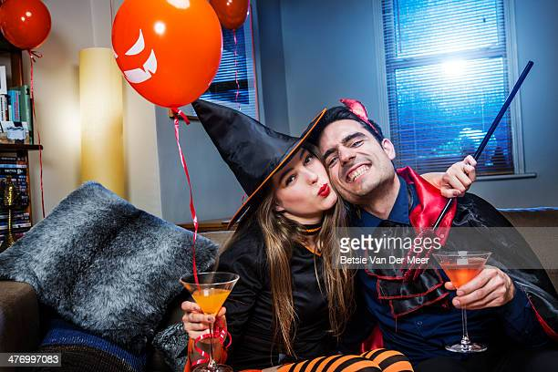 Halloween witch and devil on sofa with cocktails.