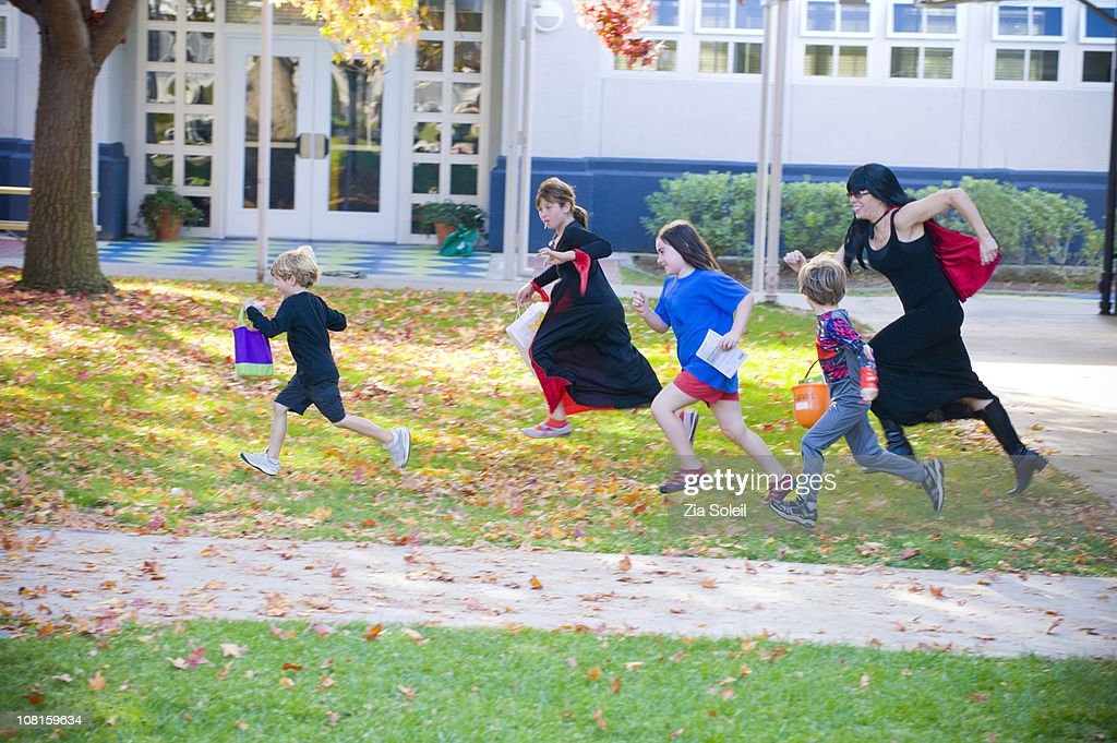 Halloween 'witch' chasing kids : Stock Photo