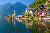 Scenic picture-postcard view of famous Hallstatt village reflecting in Hallstattersee lake in the Austrian Alps in beautiful morning light on a sunny day in summer, Salzkammergut region, Austria.