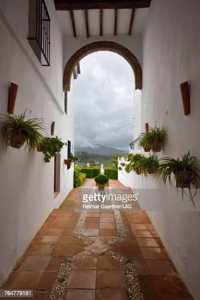 Hallway to garden patio and rain clouds at Mondragon Palace Ronda museum Spain