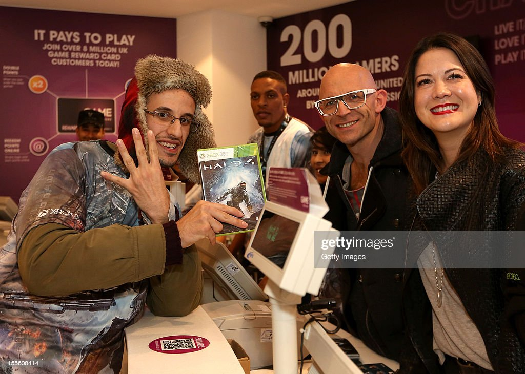 'Halo' fan Kenzie Vialli (L), the first person in line, purchases a copy of Halo 4 and poses at the register with (L-R) Jason Bradbury of 'The Gadget Show' and Executive Producer at 343 Industries Kiki Wolfkill during the launch of Halo 4 on Xbox 360 at Westfield Stratford shopping center on November 06, 2012 in London, England.
