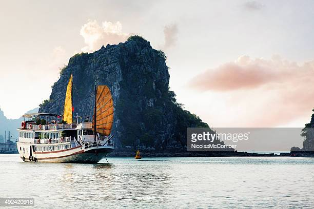 Halong bay Vietnam tourist ship with cliff island at sunset