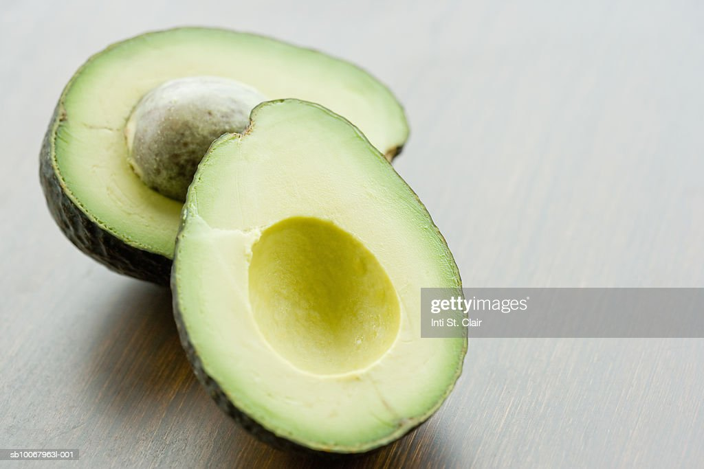 Halved avocado on tabletop, close up : Stock Photo