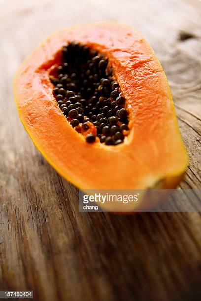 A halved fresh papaya on a wooden surface