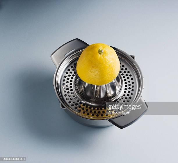 Halved lemon on stainless steel lemon squeezer