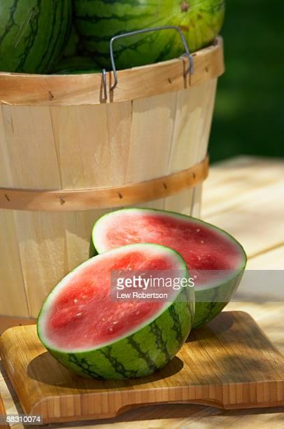 Halved watermelon and bushel basket