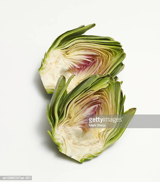 Halves of artichoke against white background
